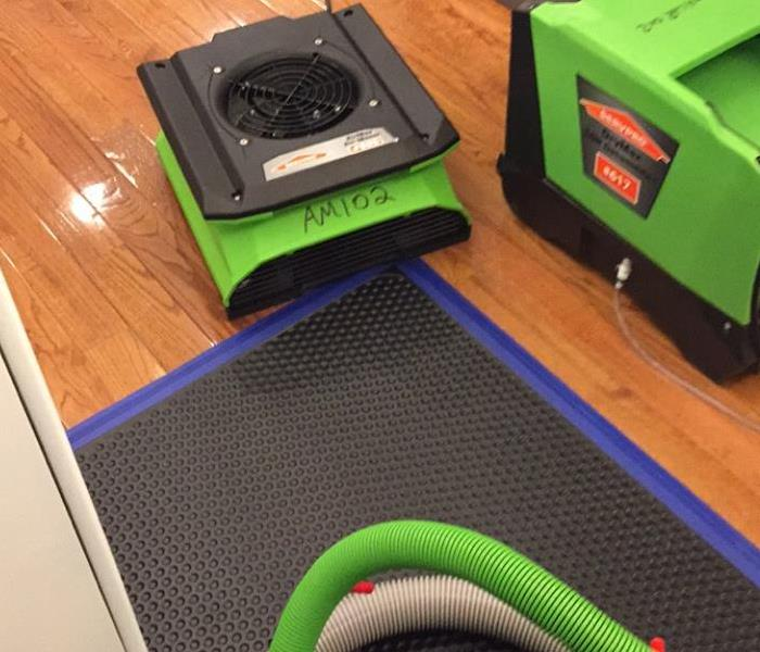 green drying equipment with hoses and mats on hardwood floor